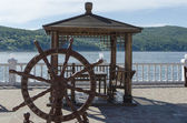 Wooden arbor with table and decorative helm on the Angara river shore — Stock Photo