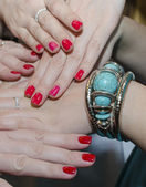 Red nails and turquoise jewelry on female hands — Stock Photo