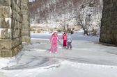 Little girls skate on Baikal ice under the viaduct — Stock Photo