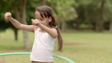 Happy young girl playing with hula-hoop in park — Stock Video