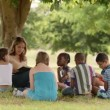 Young woman at work as educator reading book to boys and girls in park — Stock Video