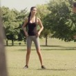 Two beautiful young women stretching muscles in city park after running and doing sport activity. Dolly shot — Stock Video