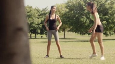 Dvě krásné mladé ženy protažení svalů v městském parku po spuštění a dělat sportovní aktivitu. dolly zastřelil — Stock video