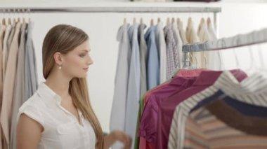 Elegir camiseta en la tienda de ropa joven — Vídeo de stock