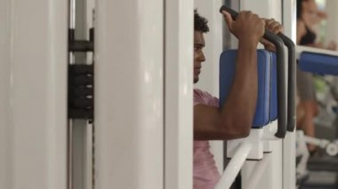Young black man exercising pectoral muscles in wellness club — Stock Video