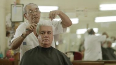 Man getting a haircut by senior barber — Stockvideo