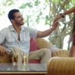 Young just married hispanic couple sitting on armchair in hotel bar and hugging — Stock Video