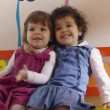Female preschoolers sitting on bench in kindergarten, playing and smiling — Stock Video