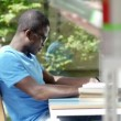 African american guy and caucasian female college student reading book in library — Stock Video #21806211