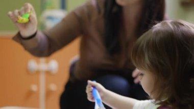 School: teacher feeding young female children during lunch time at kindergarten — Stock Video
