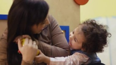Female teacher playing and laughing with little young girl in kindergarten — Stock Video