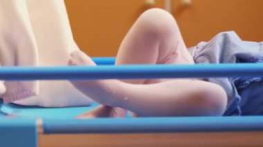 Little child going to sleep in cot at kindergarten with teacher covering her. — Stock Video