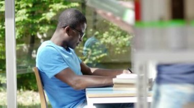 African american guy and caucasian female college student reading book in library — Stock Video