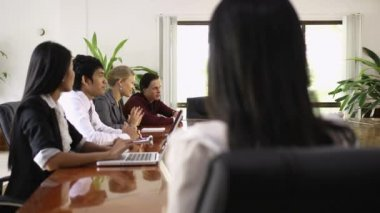 Attractive young Asian business woman smiling at business meeting with co-workers — Stock Video