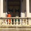 Old Buddhist monk with eyeglasses descending stairs — Stock Video
