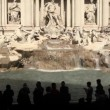 And tourists at Fontana di Trevi, Trevi Fountain in the city of Rome, Italy - Stock Photo
