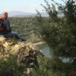 Stock Video: Adult mwith binoculars sitting on rock, looking at lake