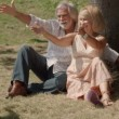 Stock Video: Seniors smiling with child and sitting on grass under tree. Slow motion