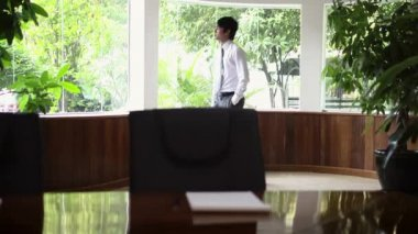 Young Asian man at work as businessman and looking out of the office windows — Stock Video