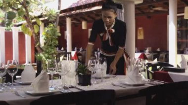 Attractive young woman working as waitress in exclusive restaurant, setting up a table. — Stock Video