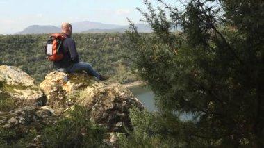 Adult man with binoculars sitting on rock, looking at lake — Stock Video