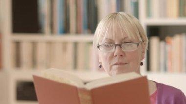 Happy senior kvinna med glasögon läser bok hemma — Stockvideo