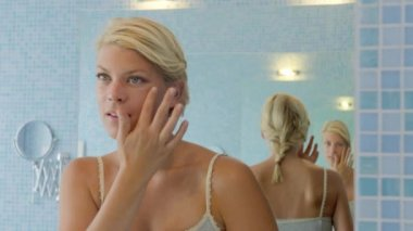 Beautiful young caucasian woman applying cream on face in bathroom at home. — Stock Video