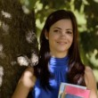 Stock Video: Happy young womsmiling with college textbooks in park leaning on tree
