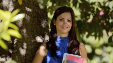 Happy young woman smiling with college textbooks in park leaning on tree — Stock Video