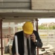 Architect talking on cell phone and walking in construction site under building scaffolding. — Stock Video