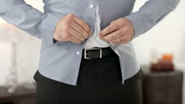 Frustrated angry businessman trying to button up a tight shirt after gaining weight — Stock Video