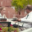 Businessman on wheelchair talking to female co-worker and using digital tablet pc. — Stock Video
