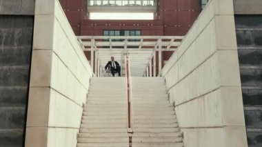 Man on wheelchair trying to descend stairs in town. — Stock Video