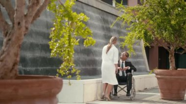 Patient on wheelchair speaking with female doctor in hospital gardens. — Stock Video
