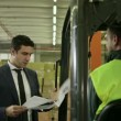 Stock Video: Businessman in shipping facility speaking with manual worker operating forklift