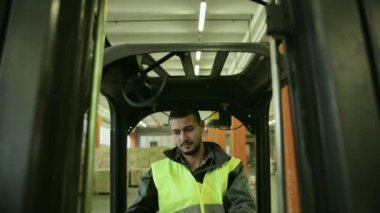 Manual worker operating fork lift to move boxes and parcels — Stock Video