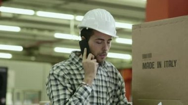 Portrait of young man employed in logistics facility talking on mobile phone — Stock Video