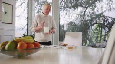 Portrait of senior woman having breakfast with milk — Stock Video