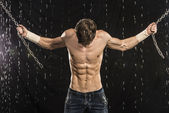 Image of muscle man with chains posing in water studio — Stock Photo