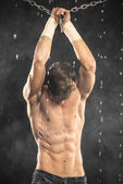Image of muscle man with chains posing in water studio on smoke — Stock Photo