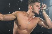 Strong man in chains posing under the rain, aqua studio — Stock Photo