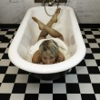 Blond girl in the vintage bath looking at you. — Stock Photo