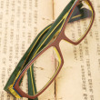 Eyeglasses on the old thick book — Stock Photo