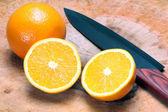 Orange with knife — Stock Photo