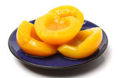 Peaches on blue plate — Stock Photo