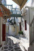 Narrow cozy street of the island of Mykonos with colorful wooden balconies early evening — Stock Photo