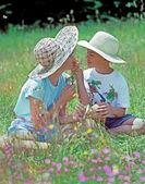 Oğlan ve kız ile kır çiçekleri — Stok fotoğraf