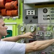 A fireman activating switches and dials on a rescue truck — Stock Photo