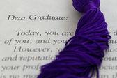 Tassel cords resting on top of graduation paperwork — Stock Photo