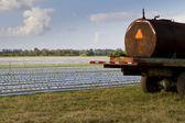 Vintage roestig landbouwgrond apparatuur met boerderij achtergrond — Stockfoto
